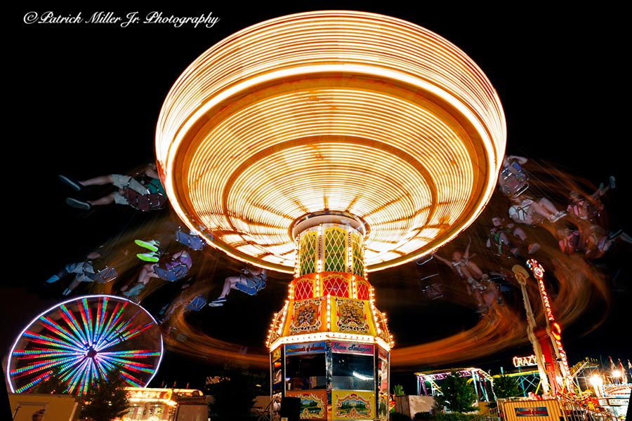 Vivid carnival swing ride at night, in motion with a long exposure time