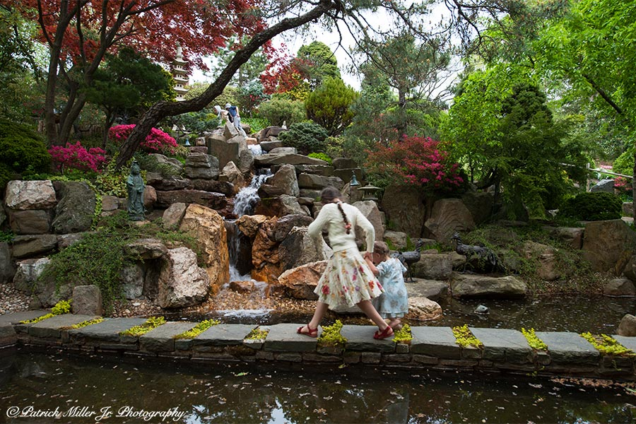 Girls crossing a stone path in Japanese Garden