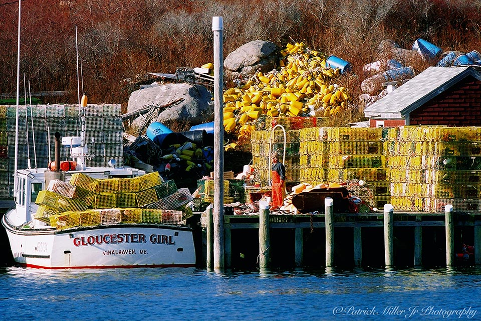"""Lobsterman on his dock full of colorful lobster equipment and his lobster boat """"Gloucester Girl"""""""