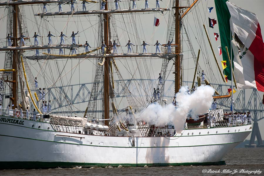 Sailers on three masts schooner as it enters Baltimore Harbor firing a cannon.