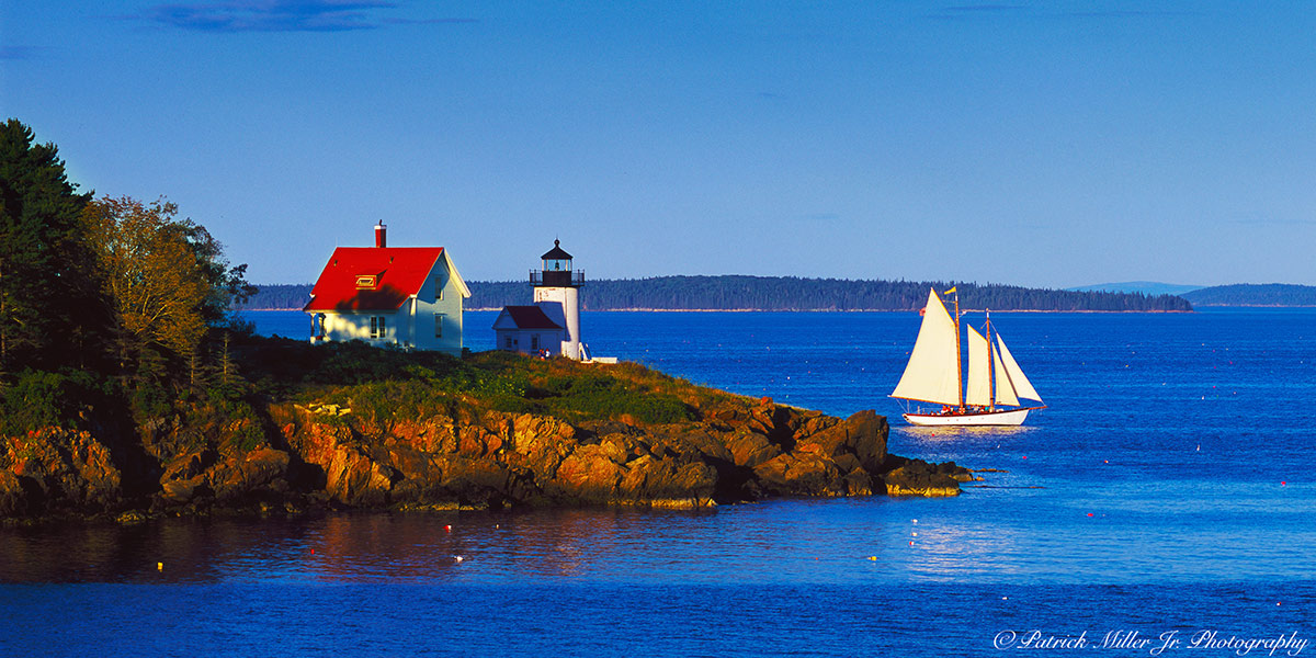 Schooner passing Curtis Island Lighthouse as the sun sets in Camden Maine.
