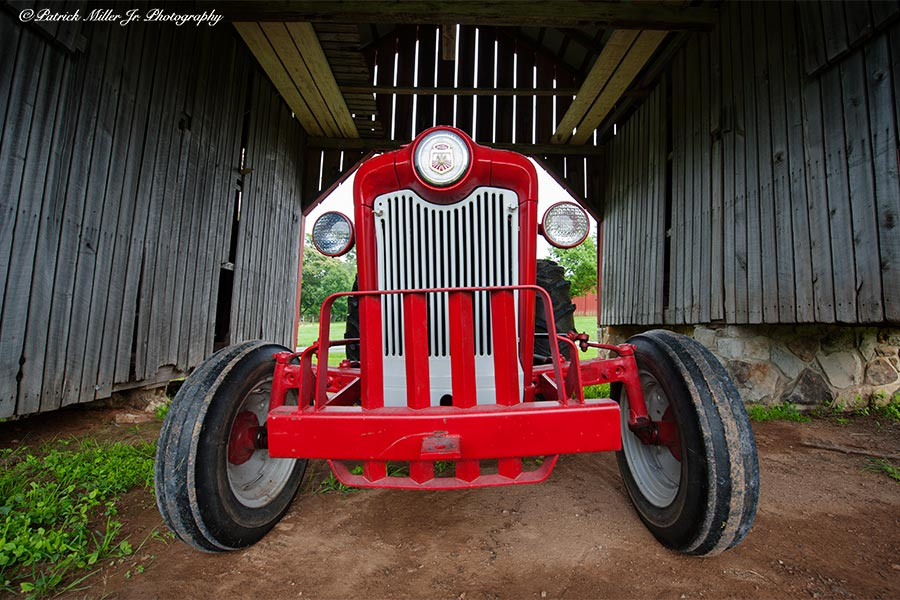 Old restored Ford tractor in a wooden barn in Maryland