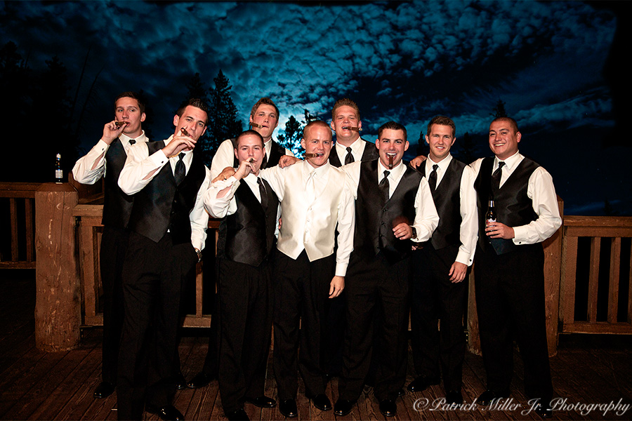 Wedding event groomsmen relaxing and smocking cigars in Colorado