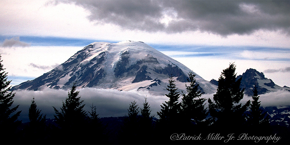 Snow covered Mount Reiner from a distance with bad weather moving in Washington State.