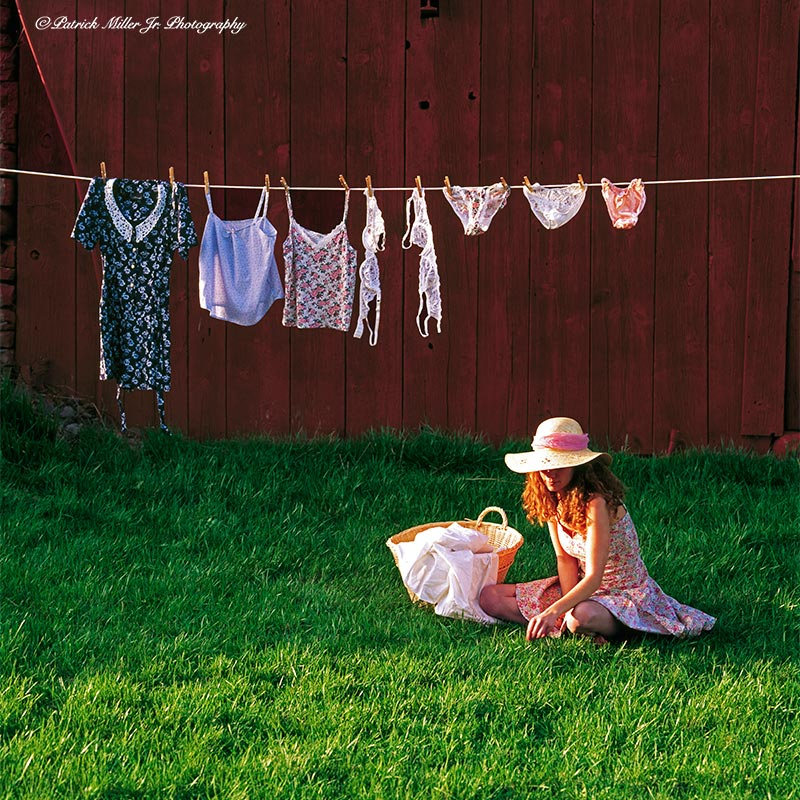 Portrait of a women in a sundress and hat under clothes line