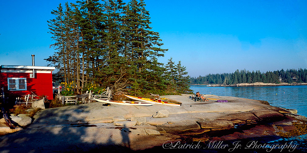 Kayakers relaxing on coast of Vinalhaven Island Maine.