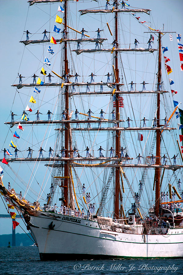 Schooner entering Baltimore Harbor with sailers on masts during Sailabration celebrations