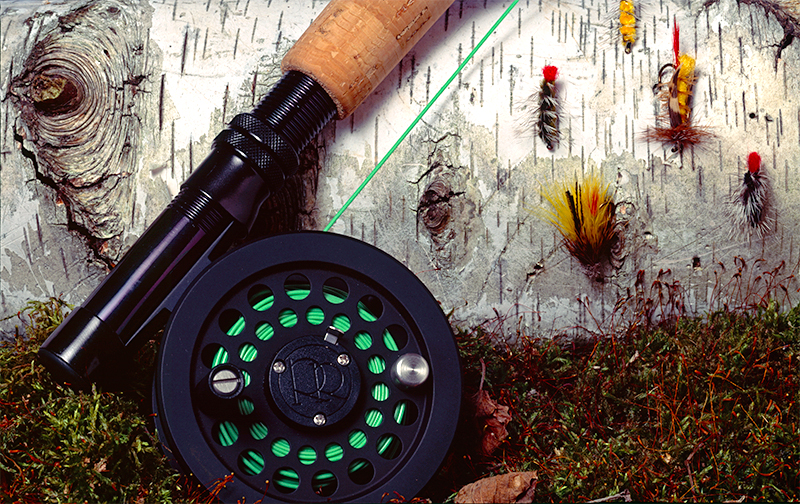 Product shot of fly rod and flies with moss and birch tree